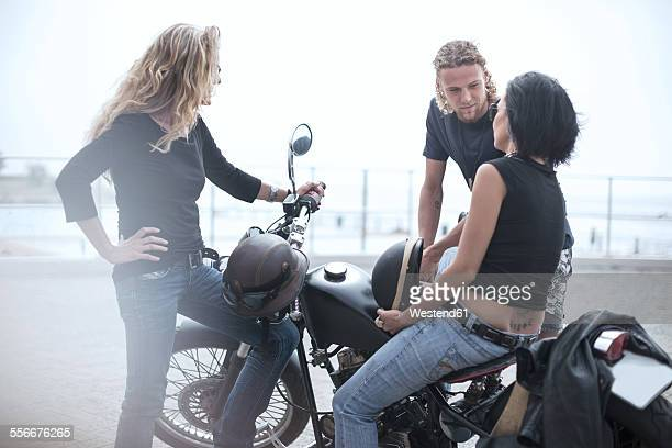 Man and two women around motorcycle