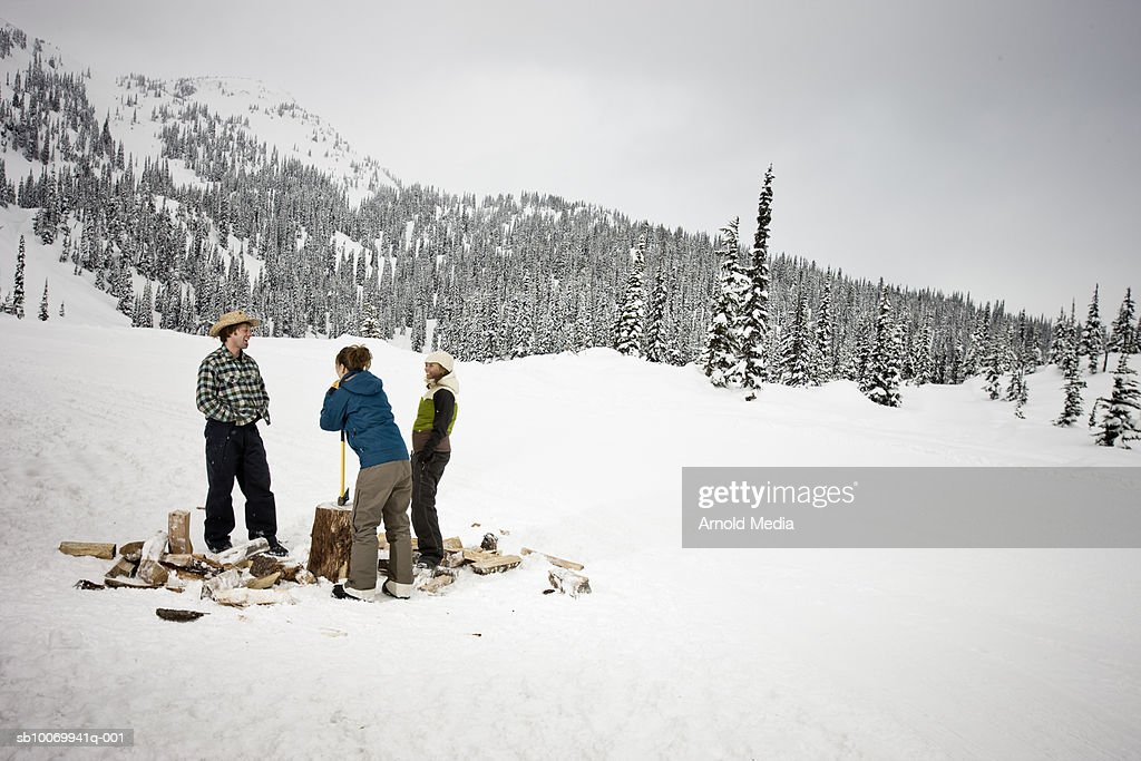 Man and two women chopping wood in mountains : Stock Photo