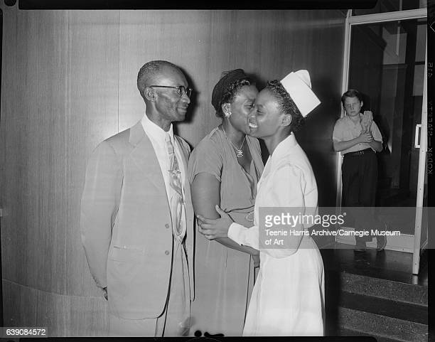 Man and two women including nurse hugging other woman in interior with boy standing on terrazzo steps in front of door on right circa 1954