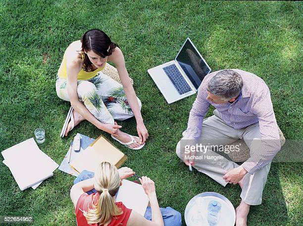 Man and two women sitting together outdoors, discussing