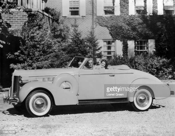 A man and two women smile with a pet Terrier while sitting in a new Buick Series 40 Convertible Coupe 1938