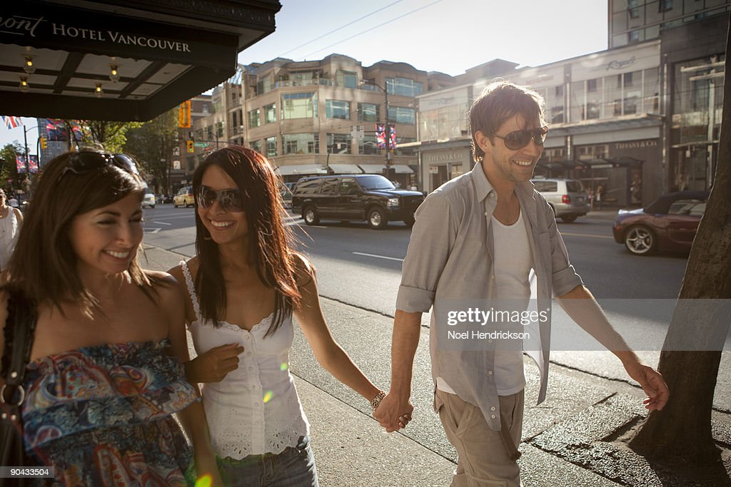 man and two women walking in city : Stock Photo