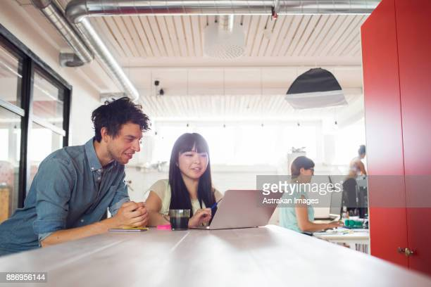 Man and two women working at office, woman standing by window in background