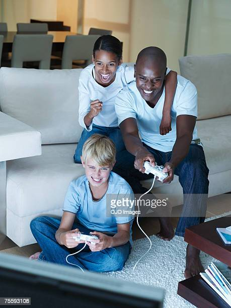Man and two young kids playing a video game