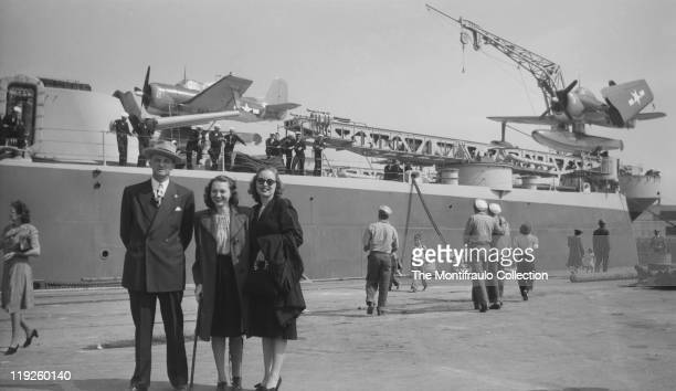 Man and two young women standing in front of an American battleship in port with two Seahawk SC1 Curtiss scout seaplanes on the top deck with one of...