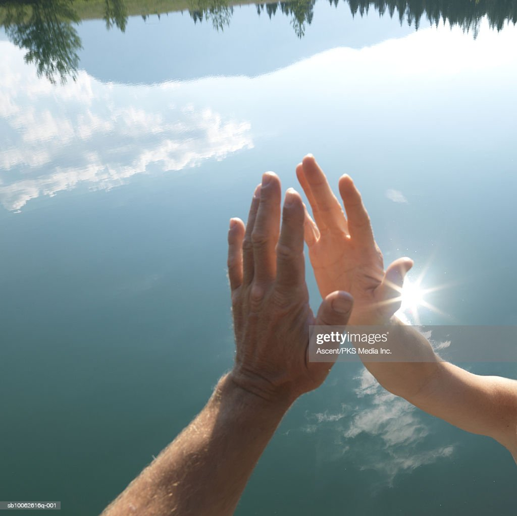 Man and woman about to clasp hands above lake, close-up : Stock Photo