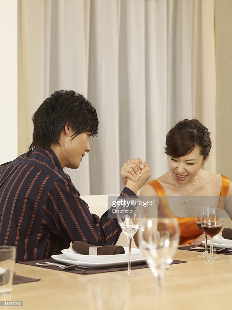 Man and woman arm wrestling at dinner table. : Stock Photo