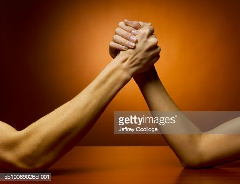 Man and woman arm wrestling, studio shot