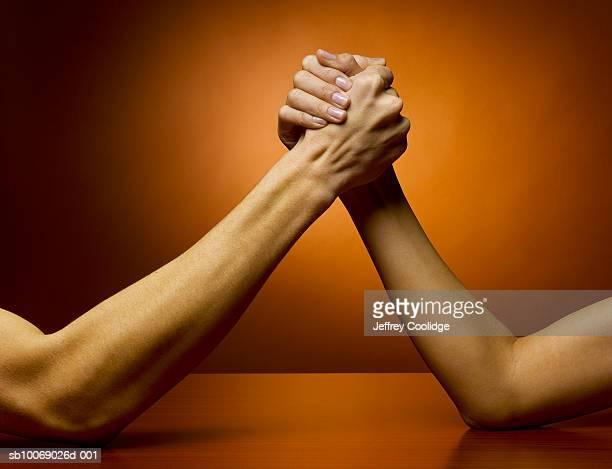 Man and woman arm wrestling, studio shot