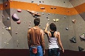 Rear view of female instructor giving instructions to a man on wall climbing. Man learning the art of rock climbing at an indoor climbing centre.