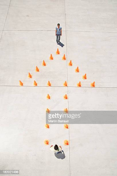 Man and woman at either end of traffic cones in arrow formation