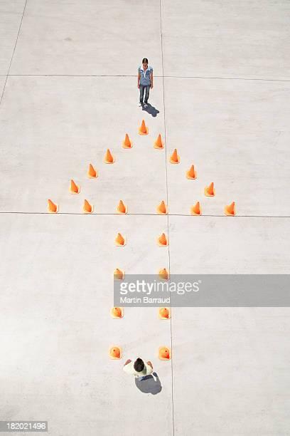 Homem e mulher em uma extremidade de cones de trânsito na seta