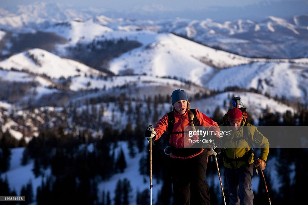Man and woman backcountry skiers reaching their summit in beautiful sunrise light.