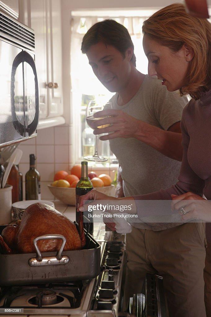 Man and woman basting turkey
