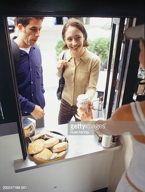 Man and woman being served at outdoor coffee cart