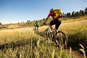 Man and woman biking on a dirt path.