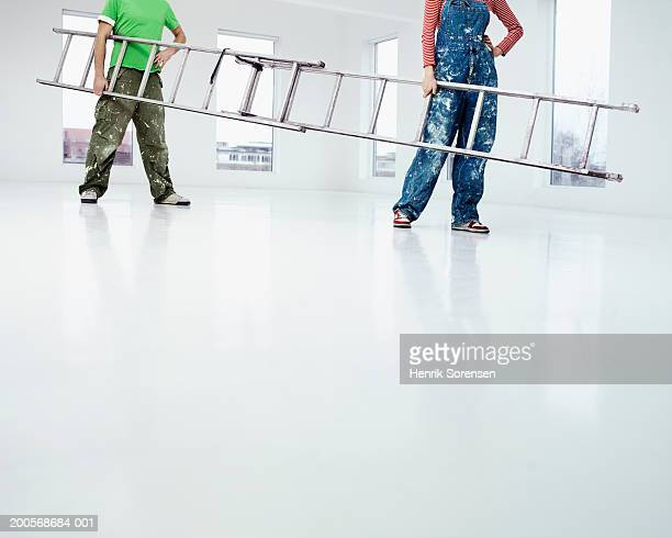 Man and woman carrying ladder in empty flat, low section