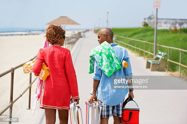 Man and woman carrying picnic equipment at beach (rear view), Spring Lake, New Jersey, USA