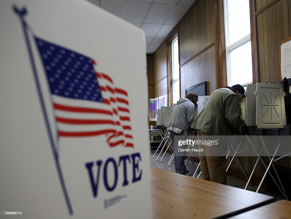 A man and woman cast their vote at a polling station on November 6 2012 in Sugar Creek Wisconsin As Americans are heading to the ballots polls show...