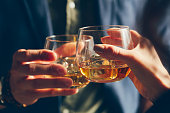 A couple makes a toast with whiskey.