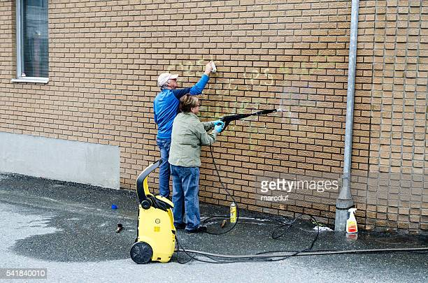 Man and woman cleaning graffiti on their brick wall
