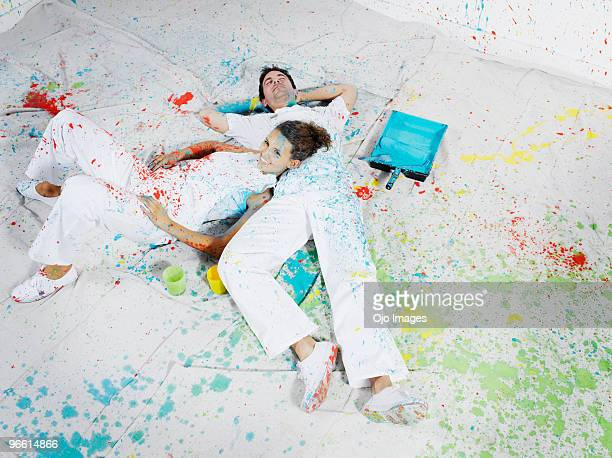 Man and woman covered in paint laying on floor