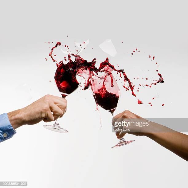 Man and woman crashing wine glasses together (Digital Composite)
