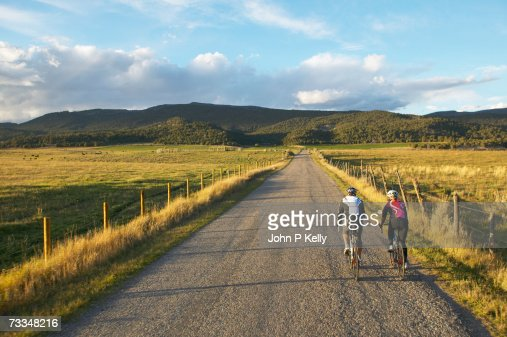 Man and woman cycling on country road, rear view