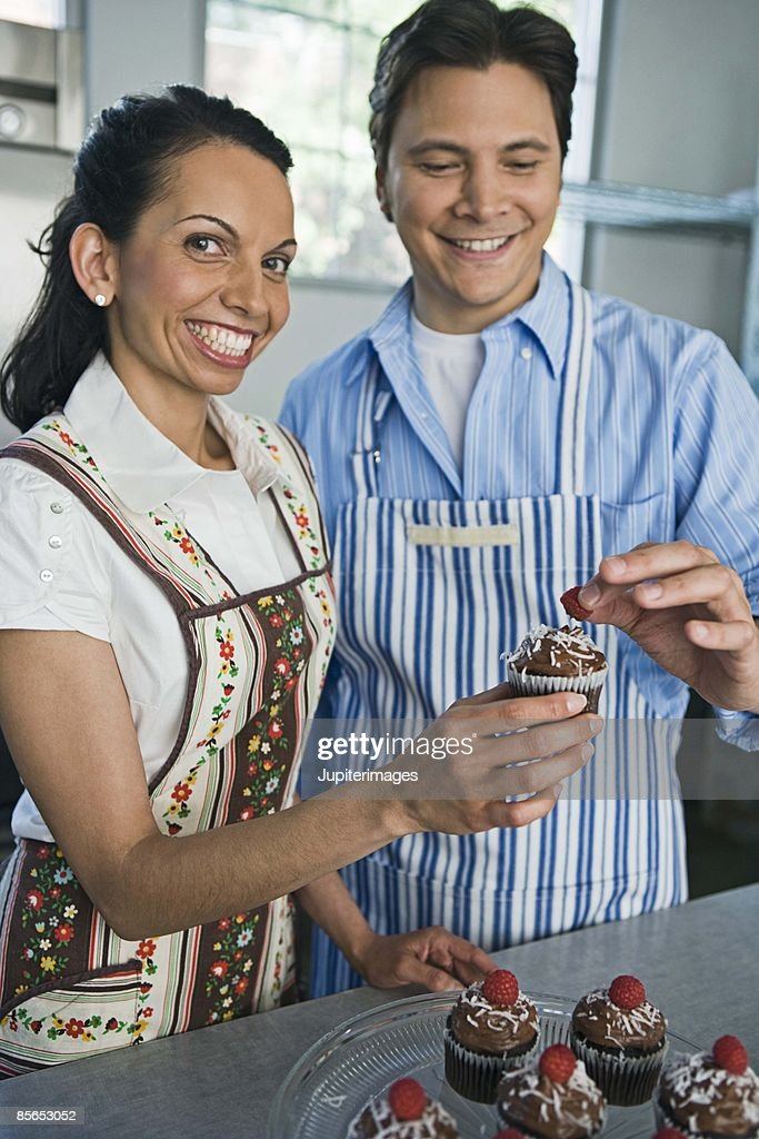 man and woman decorating cupcakes stock photo