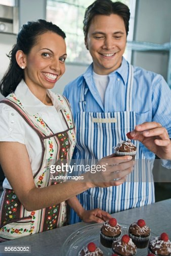 man and woman decorating cupcakes stock photo getty images - Woman Decorating Cupcakes