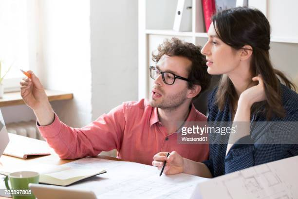 Man and woman discussing at desk in office
