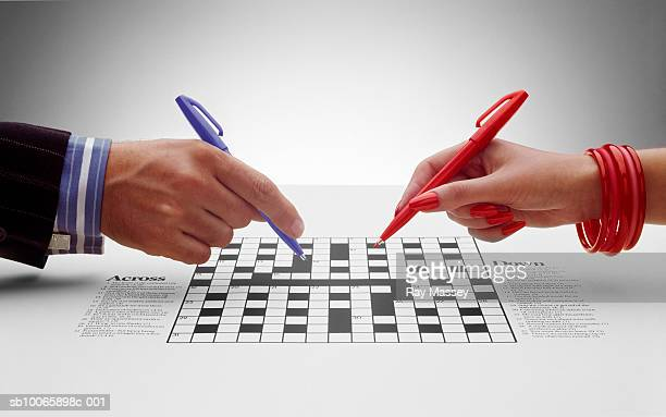 Man and woman doing crossword, close-up of hands