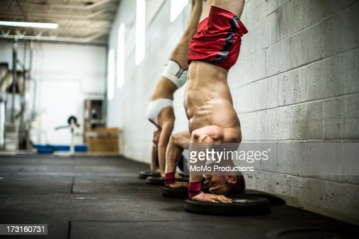 man and woman doing handstand pushups : Stock Photo