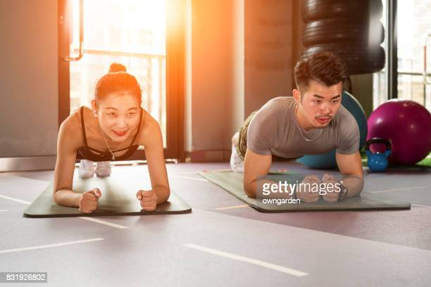 Man and woman doing planks at gym