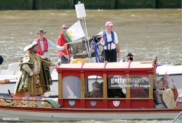 A man and woman dressed as King Henry VIII and his queen sail up the river Thames on the Royal Shallop Jubilant accompanied by an entourage of Tudor...