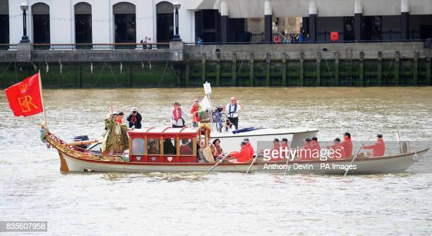 A man and woman dressed as King Henry VIII and his queen sail up the river Thames on the Royal Shallop 'Jubilant' accompanied by an entourage of...