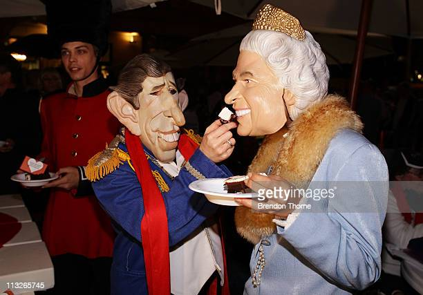 A man and woman dressed as Prince Charles and Queen Elizabeth II eat wedding cake from the live site at Customs House on April 29 2011 in Sydney...