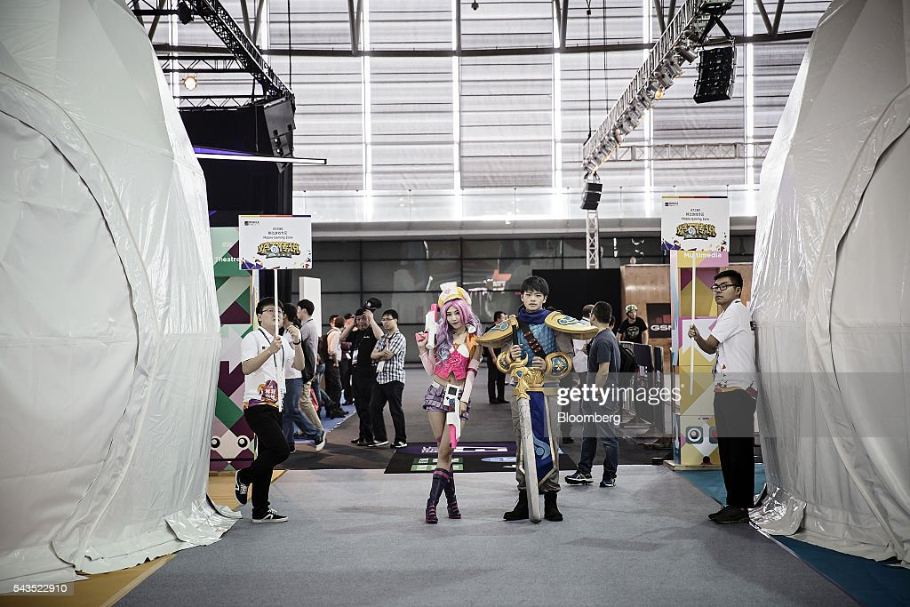 A man and woman dressed in cosplay costumes stand near a games display area at the Mobile World Congress Shanghai in Shanghai, China, on Wednesday, June 29, 2016. The exhibition runs until July 1. Photographer: Qilai Shen/Bloomberg via Getty Images