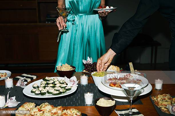 Man and woman eating appetizers at cocktail party