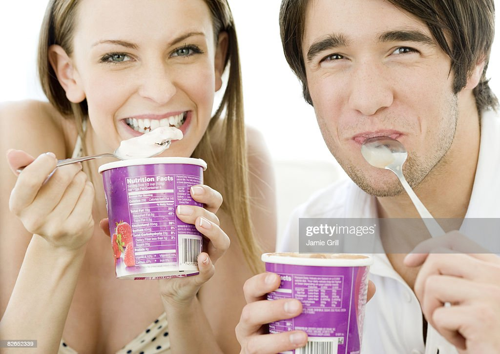 Man and Woman eating ice cream out of the cartons : Stock Photo
