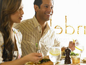 Man and woman eating meal in restaurant (focus on man smiling)