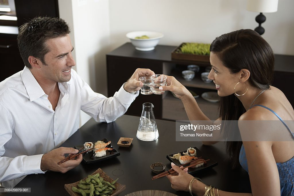 Man and woman eating sushi and toasting with sake, side view