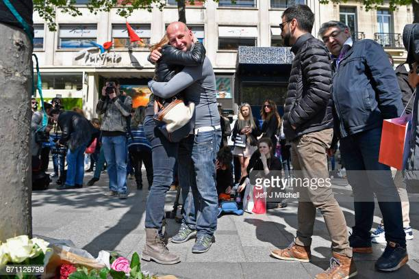 A man and woman embrace near the Marks and Spencer on the Champs Elysees in Paris following yesterday's shooting of a police officer on April 21 2017...