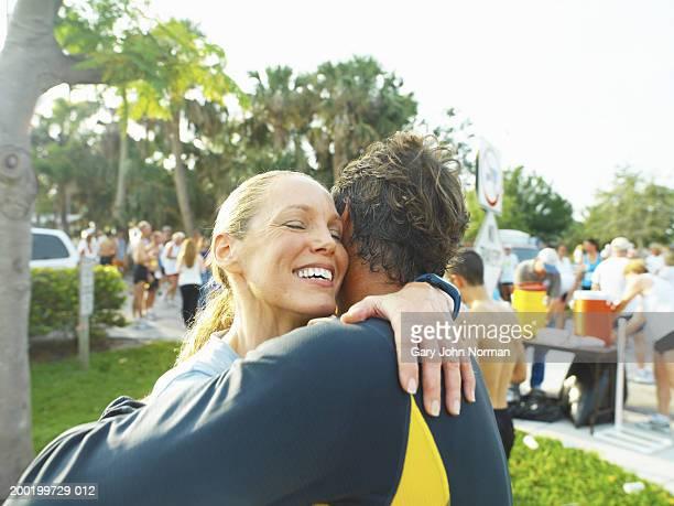 Man and woman embracing at race, close-up