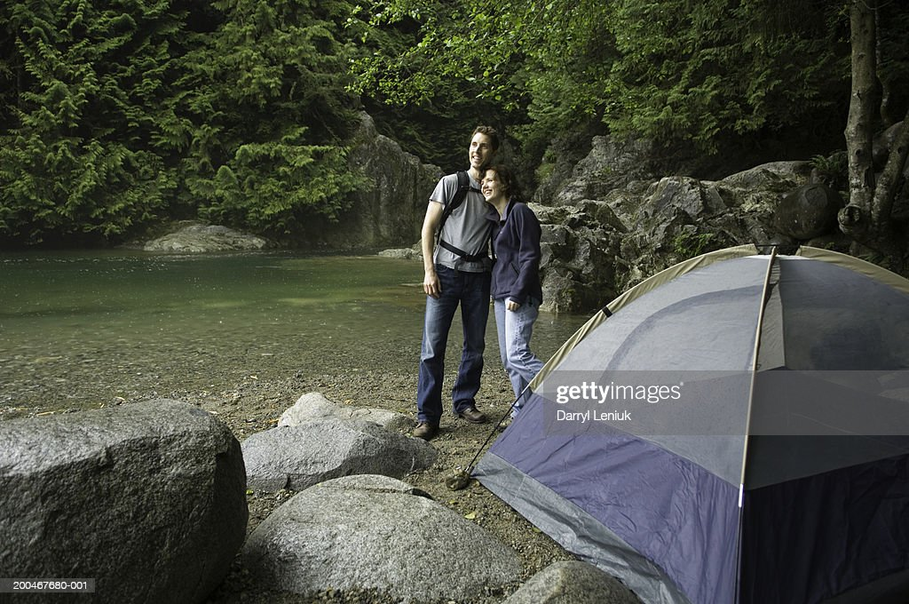 Man and woman embracing beside tent, smiling