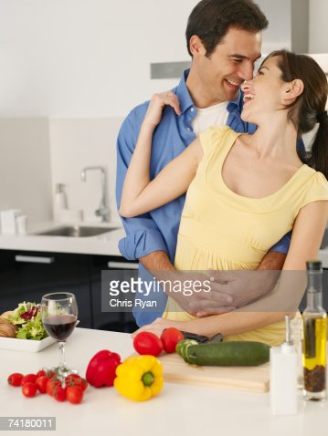 Man and woman embracing in kitchen with vegetables and red wine : Stock Photo