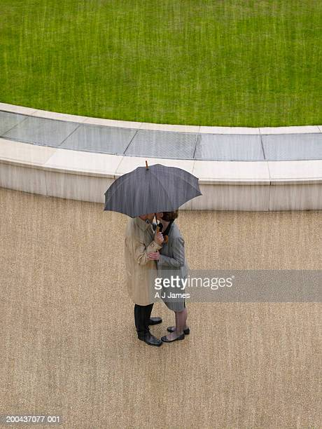 Man and woman embracing under umbrella in rain, overhead view