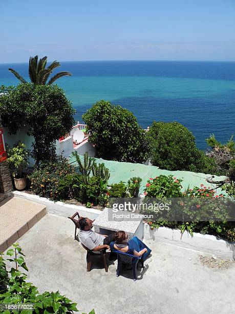 A man and woman enjoy the view of the Mediterranean Sea at the famous Cafe Hafa in Tangier, Morocco.