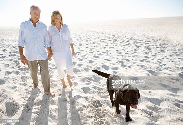 A man and woman enjoying a seaside stroll with their dog