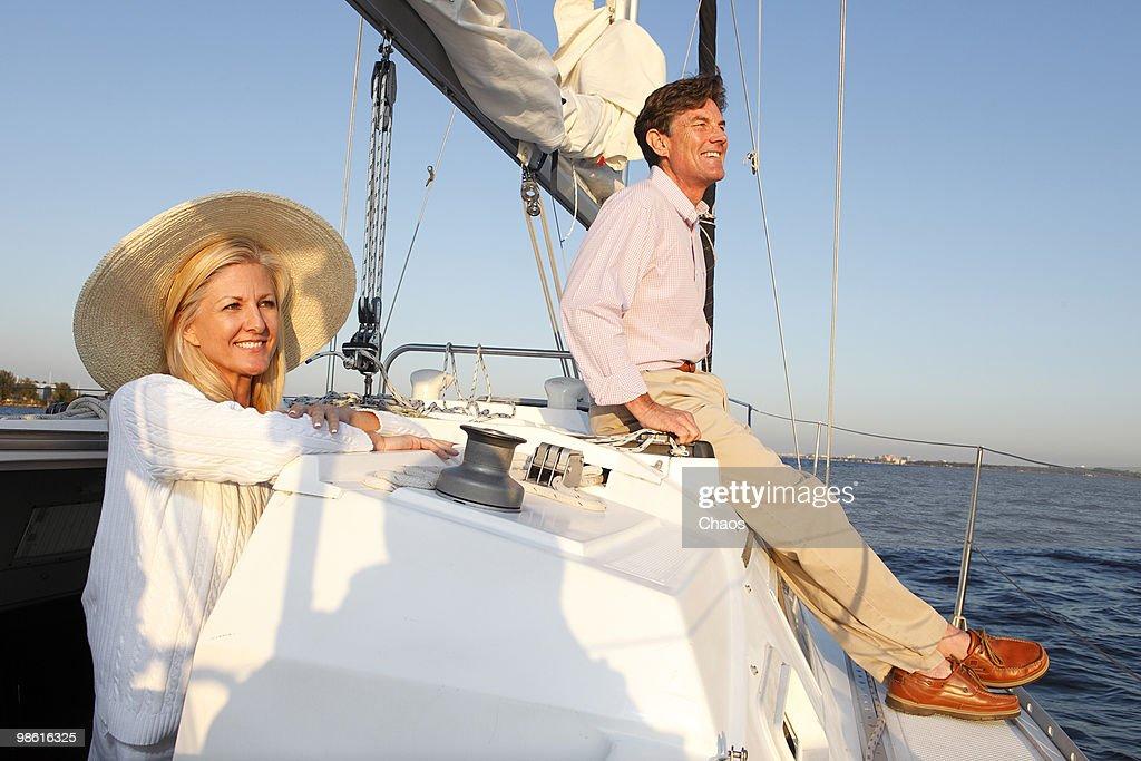 Man and woman enjoying sunset on a sailboat